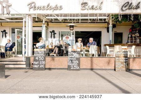 Benidorm, Spain - January 14, 2018: Tourists sitting in a sidewalk cafe in Levante beach area of Benidorm, Spain.
