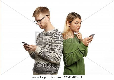 Modern technologies and internet addiction concept. Stylish young couple man and woman standing back to back, absorbed in electronic gadgets, not looking and speaking to each other, messaging online