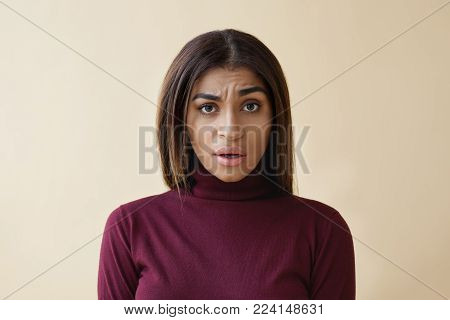 What do you mean. Portrait of confused young Afro American female feeling puzzled and indignant, raising one eyebrow and keeping mouth opened, expressing confusion, misunderstanding or dissatisfaction