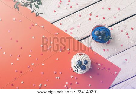 Tasty cupcakes on a wooden table. Top view Valentine's background