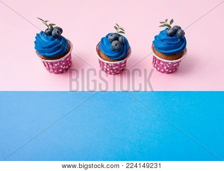 Three cupcakes in a row over two color plain background.