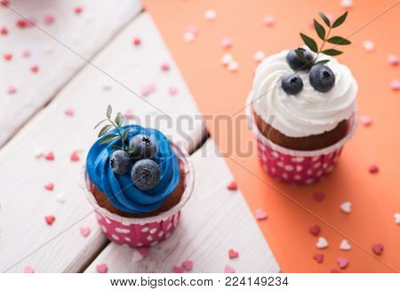 Two delicious cupcakes on a table, closeup shot