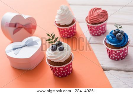 Tasty cupcakes with heart shaped gift boxes on a table