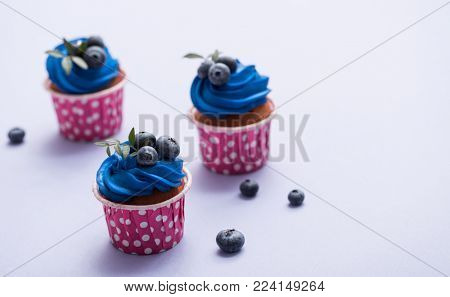 Three tasty cupcakes with blue cream over plain background.