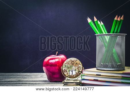 Back to School and Education concept. classroom with apple, books and pencils on chalkboard background. school border with copy space with calendar at the beginning of school.
