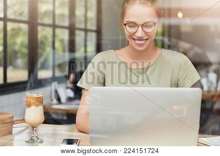 Serious Female Student Concentrated On Writing, Sits In Front Of Opened Laptop, Prepares For Classes