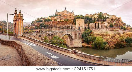 Panorama of Old city of Toledo with Alcantara Bridge across the river Tajo and Alcazar in the overcast evening, Castilla La Mancha, Spain