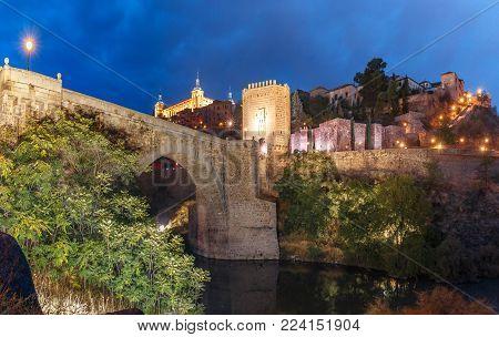 Old city of Toledo with Alcantara Bridge across the river Tajo and Alcazar at night, Castilla La Mancha, Spain