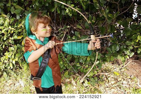 Boy playing outdoors with a bow, aiming with one eye shut. Dressed for Purim party