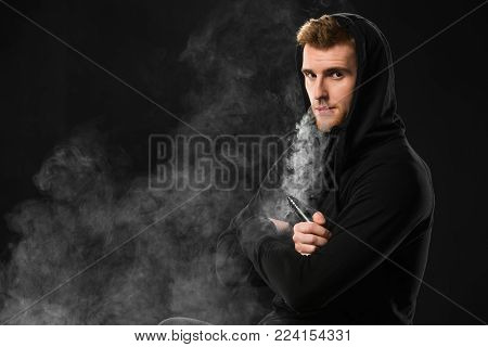 Young bearded man exhaling smoke of electronic cigarette surrounded by clouds of steam