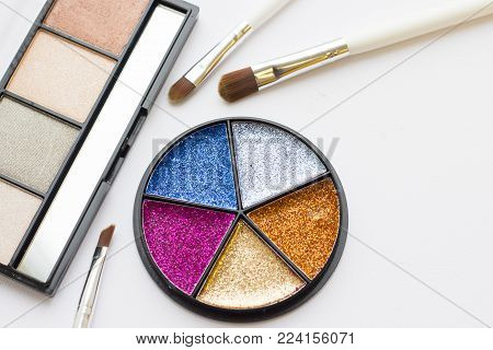 Make Up Beauty Fashion Concept. Bright glitter tinsel palette in a round box, natural colors eyeshadow palette and professional brushes on white, top view, flat lay
