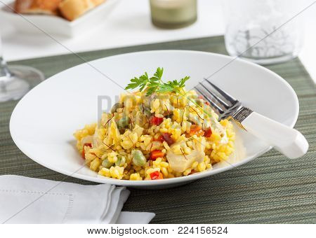 A plate of rice with vegetables and saffron.