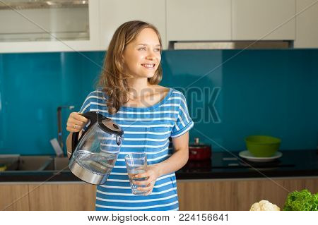 Closeup portrait of smiling young beautiful woman pouring water from kettle into glass and standing in kitchen. Drinking water concept. Front view.