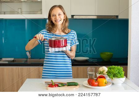 Closeup portrait of smiling young beautiful woman looking at camera, holding hot sauce pan and cooking in kitchen. Healthy cooking concept. Front view.
