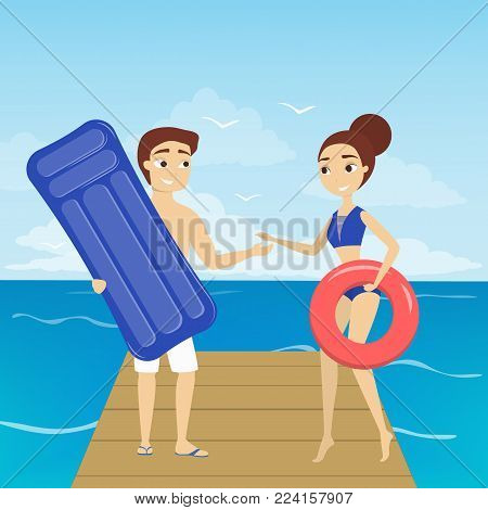 Couple at the beach standing with inflatable mattress and lifesaver.