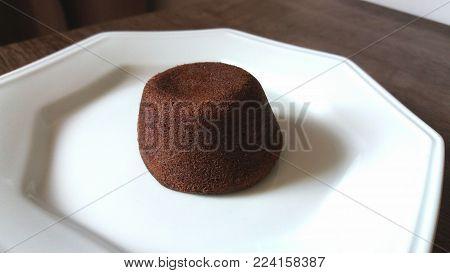 Petit Gateau. Baked chocolate dessert on white dish.
