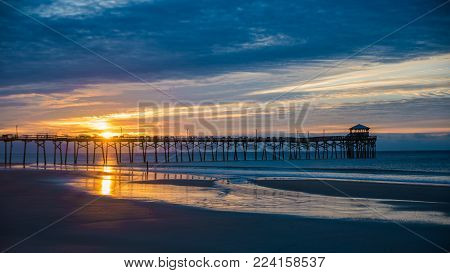 sunset at the north carolina beach with atlantic beach pier and sunrise with sand and water in the foreground