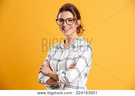 Photo of excited happy young woman standing isolated over yellow background. Looking camera.