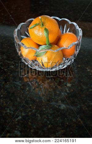 Several mandarin oranges with some leaves attached fill a pretty glass bowl on black granite.