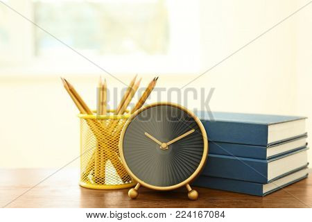 Alarm clock, stationery and stack of books on table. Time to study