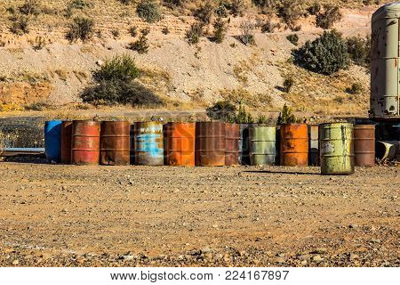 Row Of Multi Colored Fifty Gallon Drums At Salvage Yard
