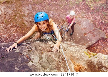High angle view portrait of young woman, rock climber in helmet, trying to reach the top of the mountains