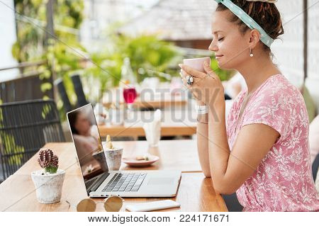 Happy Pleased Female Model With Tattoo On Hand, Wears Pink T Shirt And Head Bandage, Drinks Coffee A
