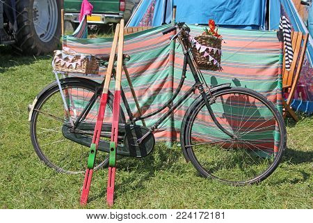 Bicycle And Stilts In A Grassy Field