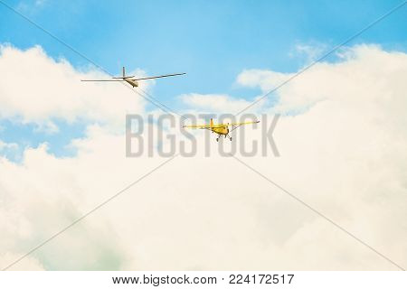 Flying in a bright cloudy sky, a yellow small sports plane with a light engine, pulls the rope by the glider plane.