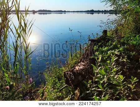 Picturesque summer evening sunset lake calm landscape with sunshine reflection in water. Concept of tranquil country life, eco friendly tourism, camping, fishing.