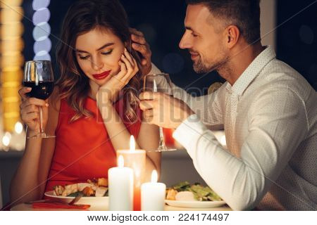 Handsome man in white shirt iron his pretty smiling girlfriend while have romantic dinner in the evening