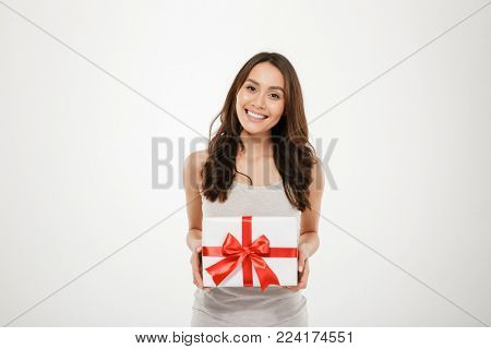 Photo of pleased woman holding box gift-wrapped with red bow being excited and surprised to get birthday present isolated over white background