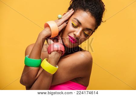 Stylish photo of beautiful african american woman with bright makeup demonstrating multicolour jewelry holding hands at face isolated over yellow