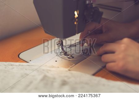 Young textile industry worker pulling the tread into the needle on a sewing machine