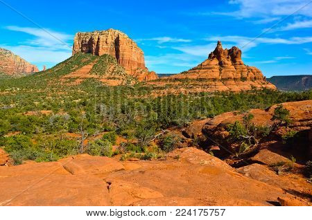 A view of Sedona's iconic Courthouse Butte and Bell Rock from a flat sandstone area called Yavapai Vista.