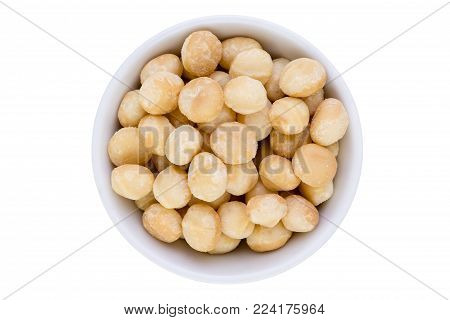 Generic white bowl of fresh healthy shelled macadamia nuts viewed close up from above isolated on white