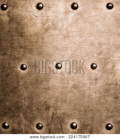 Closeup of grunge gold brown metal plate with rivets and screws as background or texture