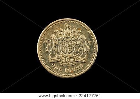A super macro image of a British one pound coin isolated on a black background