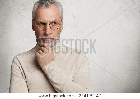 Contemplative Bearded Mature Man In Eyewear Ponders On Serious Important Question, Tries To Find Sol