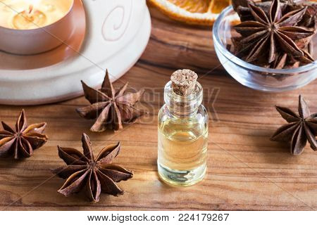 A bottle of star anise essential oil with star anise and an aroma lamp