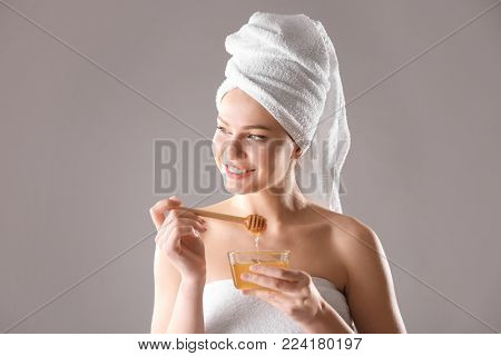 Beautiful young woman holding bowl with honey on color background
