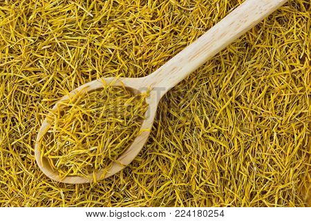 Dried Sacred Indian Lotus yellow stamen flower in wooden spoon to make herbal tea (Nelumbo nucifera)