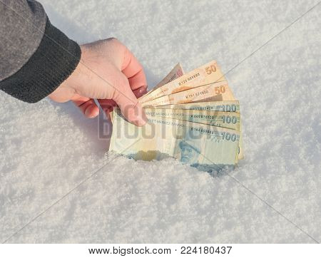 A man's hand reaches for banknotes of the Turkish Lira in the snow