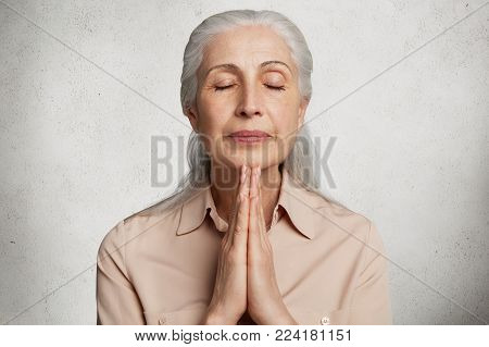 Elderly Woman Keeps Palms In Pray Gesture, Closes Eyes, Prays And Asks God For Children`s Health And