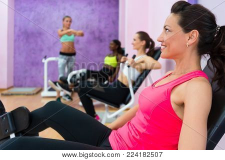 Full length side view of a fit woman laughing, while listening to the instructions of a qualified fitness instructor with sense of humor during group class for women