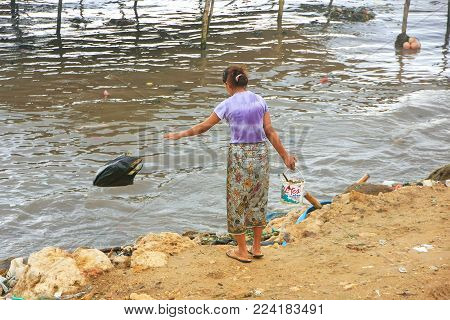 LABUAN BAJO, INDONESIA-MARCH 17: Unidentified woman throws garbage in the sea on March 17,2012 in Labuan Bajo, Flores, Indonesia. The local economy is centered around the ferry port and tourism