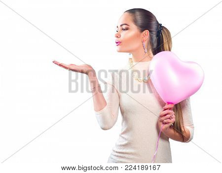 Valentine Beauty girl with pink heart shaped air balloon portrait pointing hand, isolated on white background. Beautiful Happy Young woman presenting products. Holiday party, birthday. Joyful model