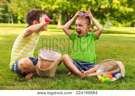 children having fun and playing with easter eggs. two cheerful boys sit on the lawn after Easter eggs hunt