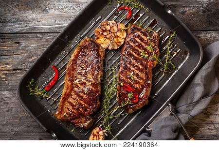 Grilled  striploin steak with spices and herbs on grill iron pan.The strip steak, also called a New York strip.