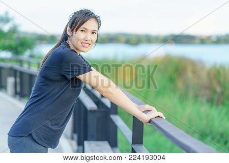Young asian woman worm up before run on nature park background